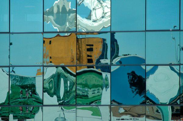 Fotografía de reflejo de edificios en fachada de cristal
