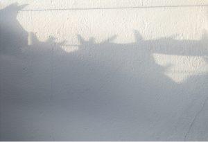 Fotografía de sombra de ropa colgada sobre pared encalada